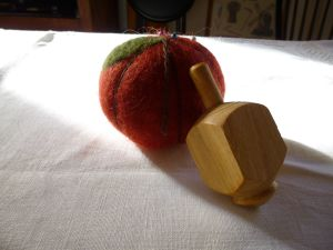 Hand-turned dreidl next to a felted pin cushion our friend Kris made