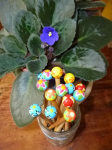Newly blooming African violet on the coffee table next to a stand of Peace Fleece knitting needles!