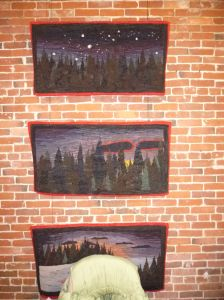 A wall of hooked rug hangings by Anne Cox