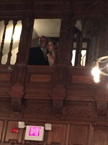 The beautiful bride and groom looking down into one of the large downstairs rooms (hors d'oeuvres time)